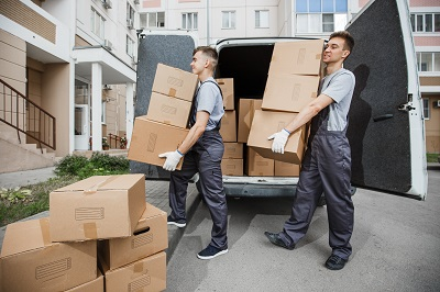 Two young handsome smiling workers wearing uniforms are unloading the van full of boxes. The block of flats is in the background. House move, mover service. local movers