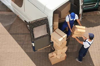 Male local movers unloading boxes from van outdoors, above view