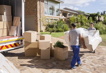 Local movers carrying sofa from moving van to house
