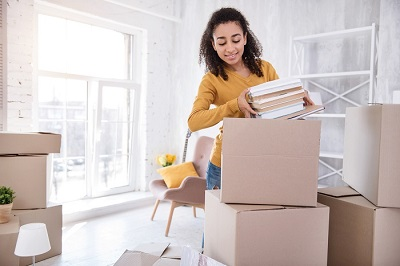 Cute curly-haired girl packing books before moving out, moving